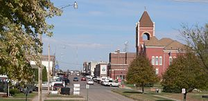 Hartington City Hall and Auditorium - Looking north on Broadway at Hartington's two most prominent brick structures, the Romanesque tower of the Cedar County Courthouse (1891-1892) appears in the right foreground, with the front (west) end of the City Hall and Auditorium across Centre Street north of the courthouse.