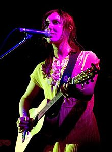 A twenty-nine year-old woman is standing at a microphone. She is playing a six-string guitar with her left had on the fret board and her right at the strings. She wears over shoulder length red-brown hair and a light coloured dress. She stares out forwards.