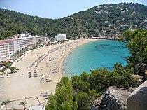 photographie rapprochée. Une petite plage de sable, encadrée d'un côté par le mur de béton formé par les hôtels et les résidences de tourisme; de l'autre côté un bout de mer bleu