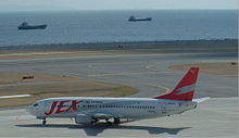 A Boeing 737-400 aircraft taxiing on the tarmac, with a seaview of two vessels in the water