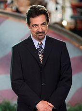 A man with a black-grey goatee in a black suit with an American flag tie