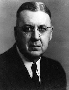 An aging, unsmiling man with round-rimmed glasses