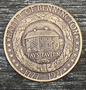 "A bronze medal, bearing the legends, ""BATTLE OF BENNINGTON"" and ""1777-1927"" and 14 stars. This surrounds a wreath with ribbons with the names of battle participants such as ""ALLEN"". Within the wreath is a building, and the inscription ""FAY'S TAVERN""."
