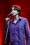 A Caucasian male with short medium brown hair. The male is wearing a purple buttoned down shirt with white designs spread across the shirt. He is standing in front of a microphone on a stand, while speaking into the microphone and clutching his right hand.