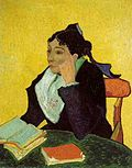 An intense woman with black hair, elbow rests on a table of books and stares to the left.
