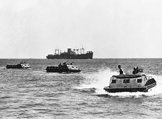 Landing Vehicle Tracked - LVT-1 move toward the beach on Guadalcanal. The USS President Hayes (AP-39) is seen in the background.