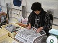 Lady folding newspaper origami boxes - for her produce, at the markets (8451648369).jpg