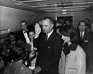 Lyndon B. Johnson being sworn in aboard Air Force One by Federal Judge Sarah T. Hughes, following the assassination of John F. Kennedy; alongside Johnson is Jacqueline Kennedy, widow of slain President John F. Kennedy