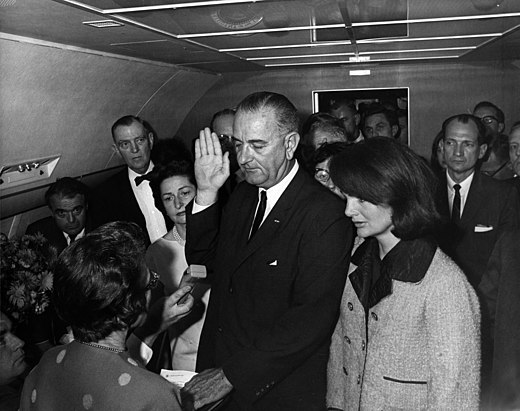 Cecil Stoughton's iconic photograph of Lyndon B. Johnson being sworn in as U.S. President aboard Air Force One, Love Field, Dallas. Jacqueline (right), still in her blood-soaked clothes (not visible in picture), looks on. Lyndon B. Johnson taking the oath of office, November 1963.jpg