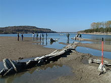 Widok na krętą rzekę za piaskownicą z ludźmi na brzegu