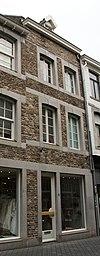 foto van Huis met lijstgevel, met horizontale reliefbanden en segmentboogvensters in Naamse steen.