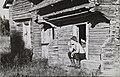 Man smoking his pipe while sitting on the steps to a traditional timber barn (34216309603).jpg
