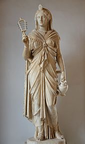 Marble staue of a woman holding a rattle in one hand and a pitcher in the other.