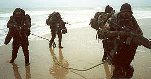 United States Marine Corps Force Reconnaissance - A four-man fireteam of Marines simulate in infiltrating a beachhead to gain information about the enemy and its adjacent beaches to help forecast a 'ship-to-shore' landing operation as seen in the 1985 2nd Force Reconnaissance Company, II Marine Expeditionary Force, MCB Camp Lejeune, NC image above (from right to left) Team Leader LCpl James Scwarhz, LCpl Lawrence Gentile, Cpl Michael Norton and LCpl Samuel Marquet.—example of green operations.