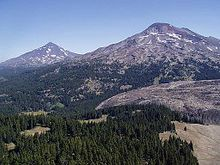 An aerial image displays Middle Sister on the left and South Sister to the right above the vegetation of the Three Sisters Wilderness.