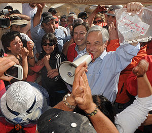 2010 Copiapó mining accident - Piñera holds the message sent by the miners alongside Mining Minister Golborne (red jacket, blue shirt)