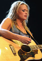 A young woman with long blonde hair playing a guitar