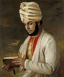 Karim in a turban and holding a book