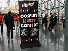 "Tall black standing sign with the phrase ""Cosplay Is Not Consent"" in large lettering, alongside New York Comic Con branding and further explanatory text in smaller lettering."