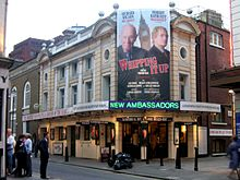 Exterior view of theatre with large poster advertising the current attraction.