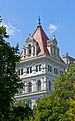 Northeast tower of New York State Capitol framed by trees.jpg