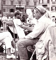 A photograph depicting Italian xpressionist painter Paolo Salvati while painting in Piazza Navona