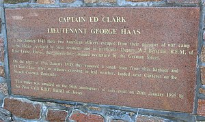 "Resistance in the German-occupied Channel Islands - Plaque at Gorey: ""Captain Ed Clark, Lieutenant George Haas escaped on 19 January 1945. This tablet was unveiled on the 50th anniversary of this event by Sir Peter Crill KBE, Bailiff of Jersey."""