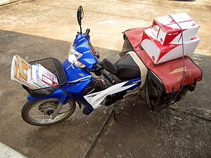 Motorcycle courier - Thailand Post bike loaded with letters and parcels