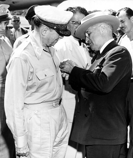 President Harry S. Truman awards the Distinguished Service Medal, Fourth Oak Leaf Cluster, to Gen. Douglas MacArthur during the Wake Island Conference. President Truman pinning medal on General MacArthur on Wake Island.jpg