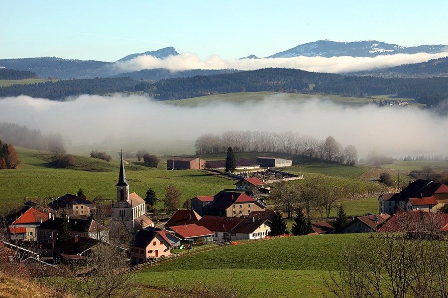 Le village de Remoray dans la brume. Au fond, l'Aiguille de Baulmes et le Suchet.