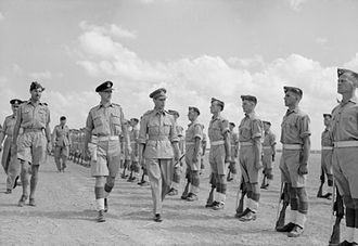 Laurence Sinclair - Air Commondore Sinclair escorts King George VI while inspecting an RAF Regiment guard of honour, at Hammamet, Tunisia, 1943.