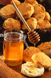 A jar of honey, shown with a wooden honey server and scones.