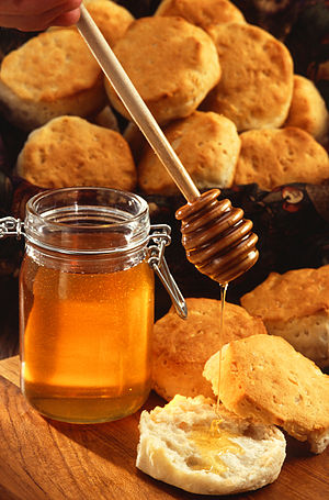 Honey - A jar of honey with a honey dipper and an American biscuit