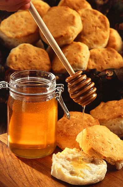 A jar of honey with honey dipper.