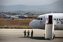 Russian Air Force Sukhoi Su-24 passes a Syrianair Airbus A320 at Latakia.jpg