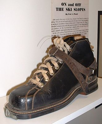 "Ski boot - A typical ""universal"" ski boot of the leather era. This example, by G. H. Bass, includes an indentation around the heel where the cable binding would fit, and a metal plate at the toe for a Saf-Ski release binding. The leather strap is a ""long thong"", used by downhill skiers to offer some level of lateral control."