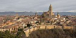 View of the back façade of the Segovia Cathedral, the ancient City Walls (8th century), and the Guadarrama mountains.