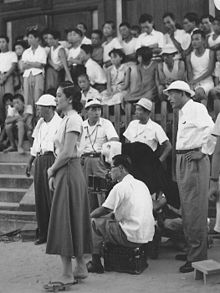 A crowd of people gathered at a film location shoot: in the background, slightly out of focus are many adults and children, some standing, some sitting on stone steps; in the left foreground is a young Japanese woman, Hara, in a white blouse and dark dress, with camera crew behind her; a middle-aged Japanese man, Ozu, in dark pants, white shirt and floppy hat stands at far right foreground.