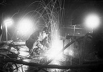 Harland and Wolff - A burner operating at night on the deck of a ship at Harland and Wolff's Liverpool yard (27 October 1944).