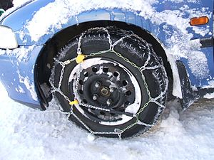Snow chains - Link-type, diamond pattern snow chains on a front-wheel drive automobile.