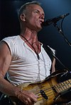 A man with a v-neck, white t-shirt wearing a necklace and bracelet standing behind a microphone, holding a guitar.