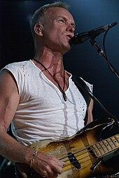 Un homme en chemise blanche debout derrière un pied de micro et tenant une guitare