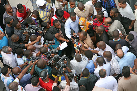 Photo and broadcast journalists interviewing a government official after a building collapse in Dar es Salaam, Tanzania. March 2013. Suleiman Kova and media, 2013 DSM Building Collapse.jpg