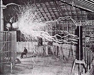 Una foto pubblicitaria di Nikola Tesla seduto nella stazione sperimentale di Colorado Springs con il suo trasmettitore d'amplificazione. Gli archi sono lunghi circa 22 piedi (7 metri).