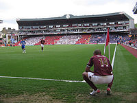 A coloured photograph of a man, crouching down on the right side. He is wearing a redcurrant shirt with white shorts; the shirt has 'Henry' and the letter 14 printed on the back. The landscape of the photograph is a filled section of a stadium.