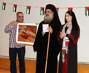 Theodosios (Hanna) - The Palestinian filmmaker and artist Hisham Zreiq honors the Archbishop of Sebastia Theodosios (Atallah Hanna), and the Palestinian singer Manl Mousa by giving each of them one of his artworks during Palestinian Land Day celebration in Dortmund, Germany