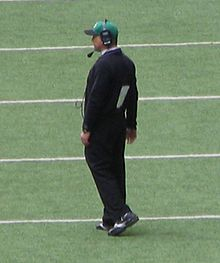 A horizontal photograph of a man standing on a football field