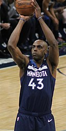 Hip high view of man raising the basketball above his head preparing to shoot a free throw, wearing navy blue Timberwolves uniform