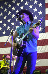 A man with his eyes closed, singing into a microphone, and playing an acoustic guitar. He is wearing a cowboy hat with blue jeans and a sleeveless blue dress shirt. A large American flag appears in the background, as do two band members.
