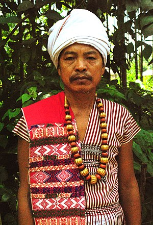 Karbi people - A Karbi man of West Karbi Anglong in traditional attire, wearing a Poho (white turban), a choi-hongthor (woven jacket), a lek paikom (gold-plated necklace) and another poho on his right shoulder.